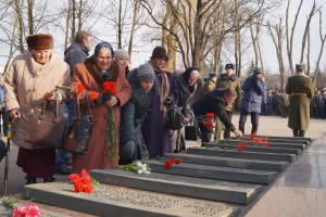 Матери, жены и дети павших воинов возлагают цветы к мемориальным плитам с именами героев